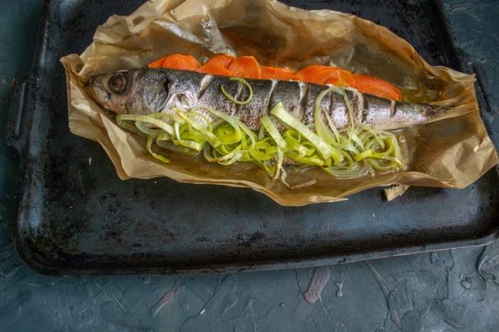 Достаём рыбу из духовки, оставляем запечатанной на 5 минут, затем разрезаем бумагу
